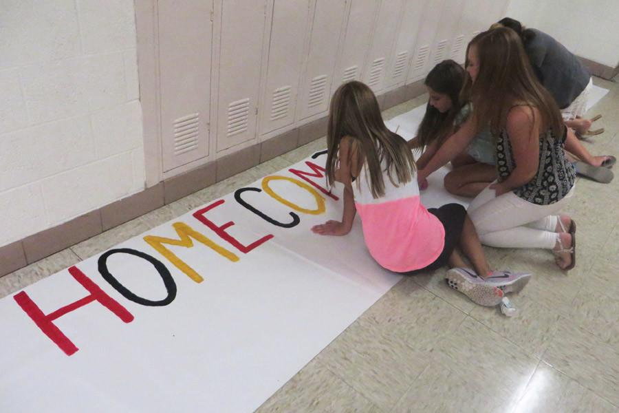 Student Senators paint a Homecoming poster in the hallway on Sept. 4.