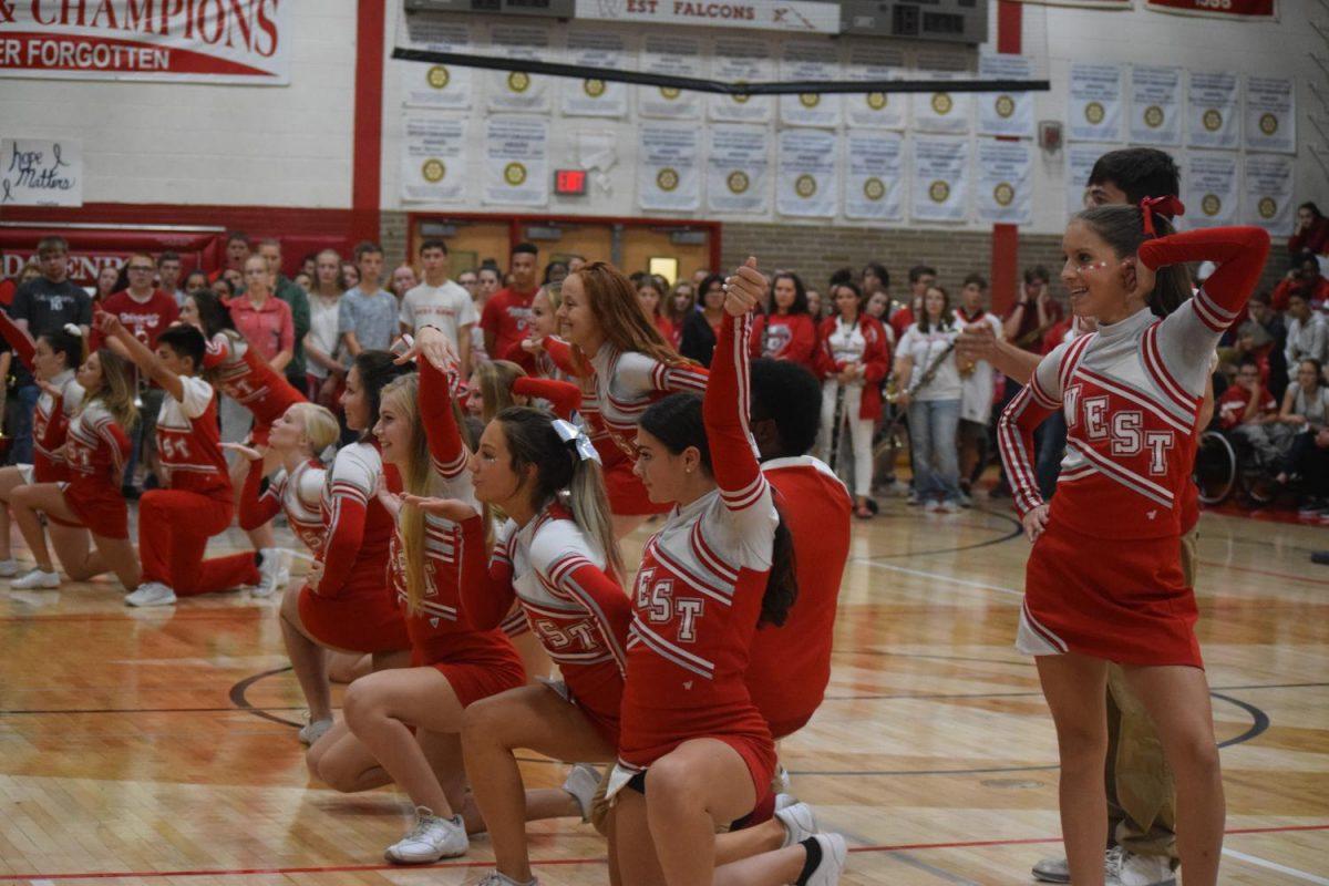 Varsity cheerleaders pumping up the crowd at pep rally.