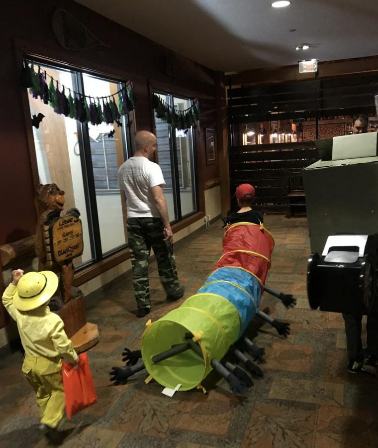 A father takes his toddler sons trick-or-treating through a hotel on Halloween.