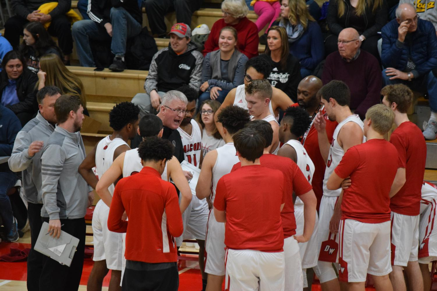 Varsity boys basketball huddle before the next play.