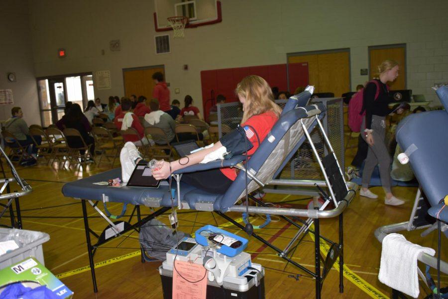 Junior Dani Reitz does her homework while donating blood.