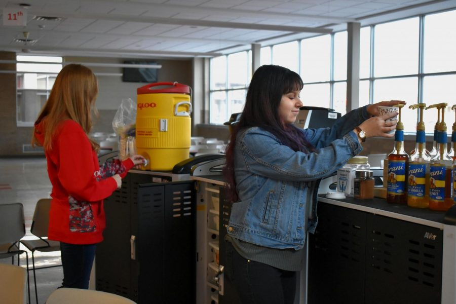 NHS treasurer Whitney Martinez putting a shot of flavor into a cup of espresso while secretary Heather Statz is getting another order prepared.