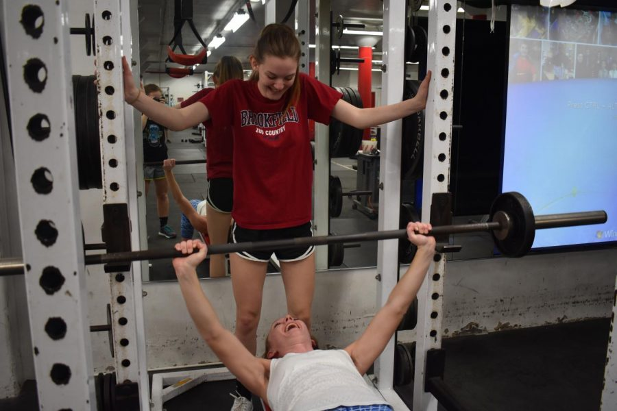 While lifting, junior Sarah Kakert pushes senior Savanah Strunk by cheering her on.