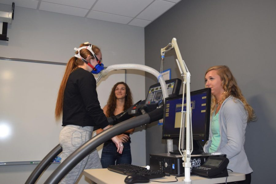 Juniors Kate Kealey, Grace James and Lauren Oostendorp run on a treadmill to test oxygen consumption.