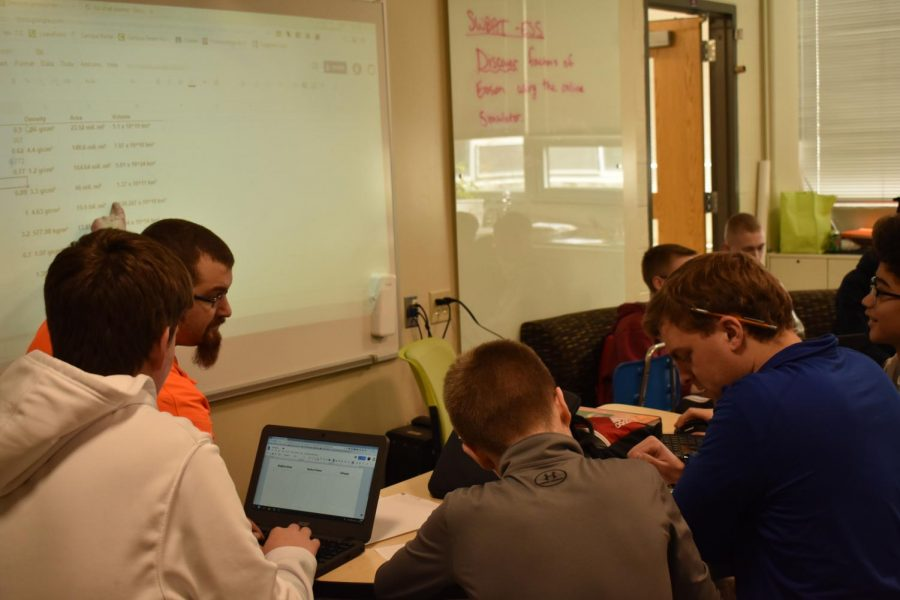 IGESS teachers Ryan DeGeeter and Jason Hensel assist a group with an assignment.