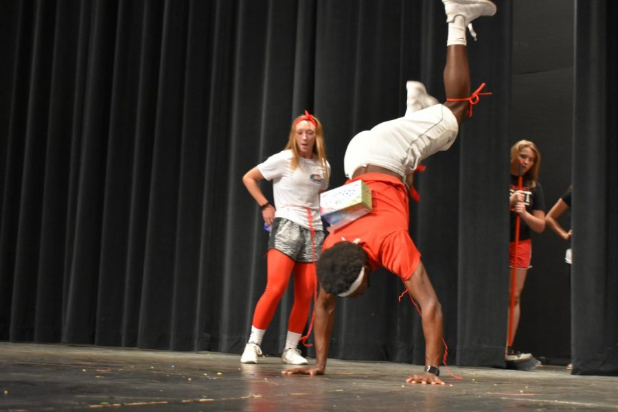 Senior Tyler Williams does a handstand in order to get the plastic balls out of the container in one of the many activities the couples participated in.