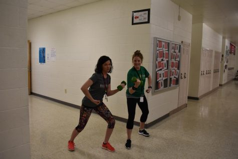English teachers Katie Choate and Alissa Hansen bulk up for the summer during five-minute passing time in honor of Workout Wednesday.