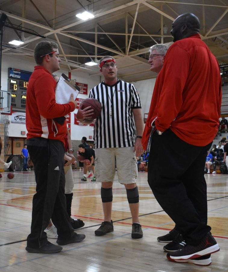 Referee Justin Peters talks to coach of the seniors Kyle Oberbroackling, head boys basketball coach Mark Bigler, and security guard David Robinson before the game.
