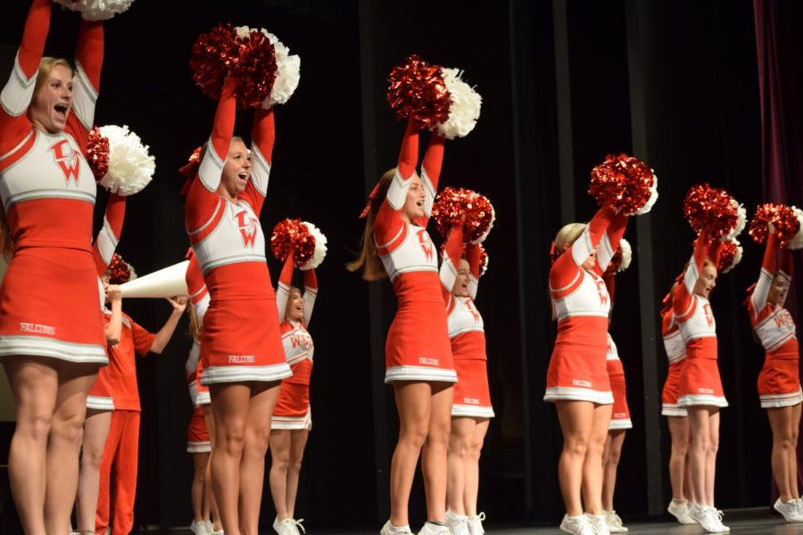 West cheerleaders perform the fight song to pump up the crowd before the kickoff.