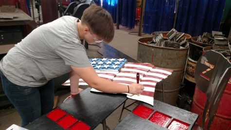 Junior Madison White hand paints the American flag.
