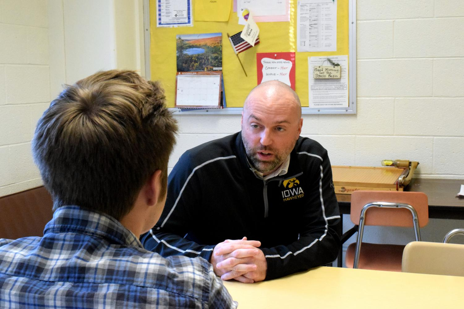 Shiltz poses speaking to a student, handling a plausible situation in which he must calm a boy or girl down in order to have a serious discussion to change the behavior which must be fixed.