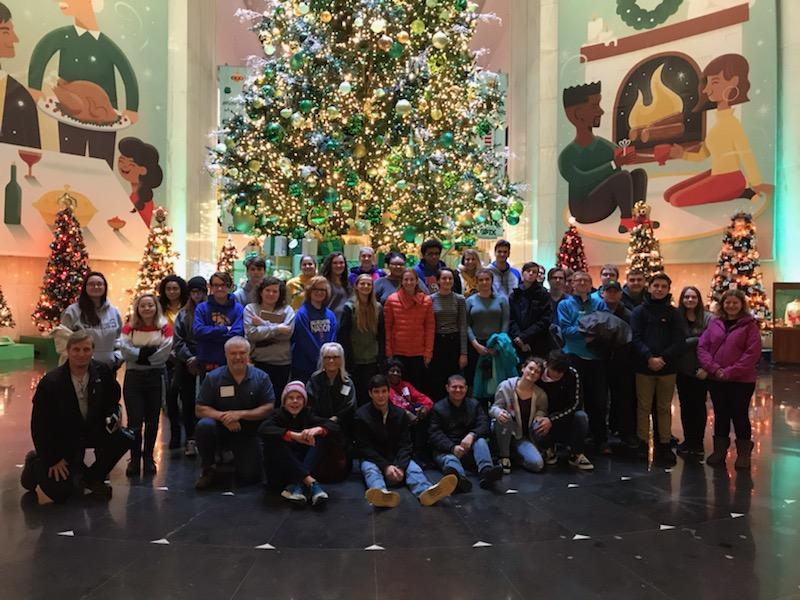 Students from West High School stand by the German Christmas tree at the Christmas trees around the world exhibit at the Science and Industry Museum in Chicago.