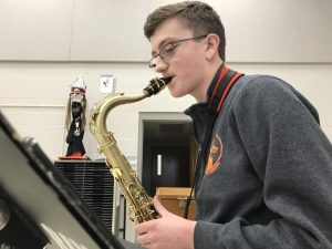 Senior William Zogg plays the saxophone, practiced hands flying across the keys of the instrument with style.