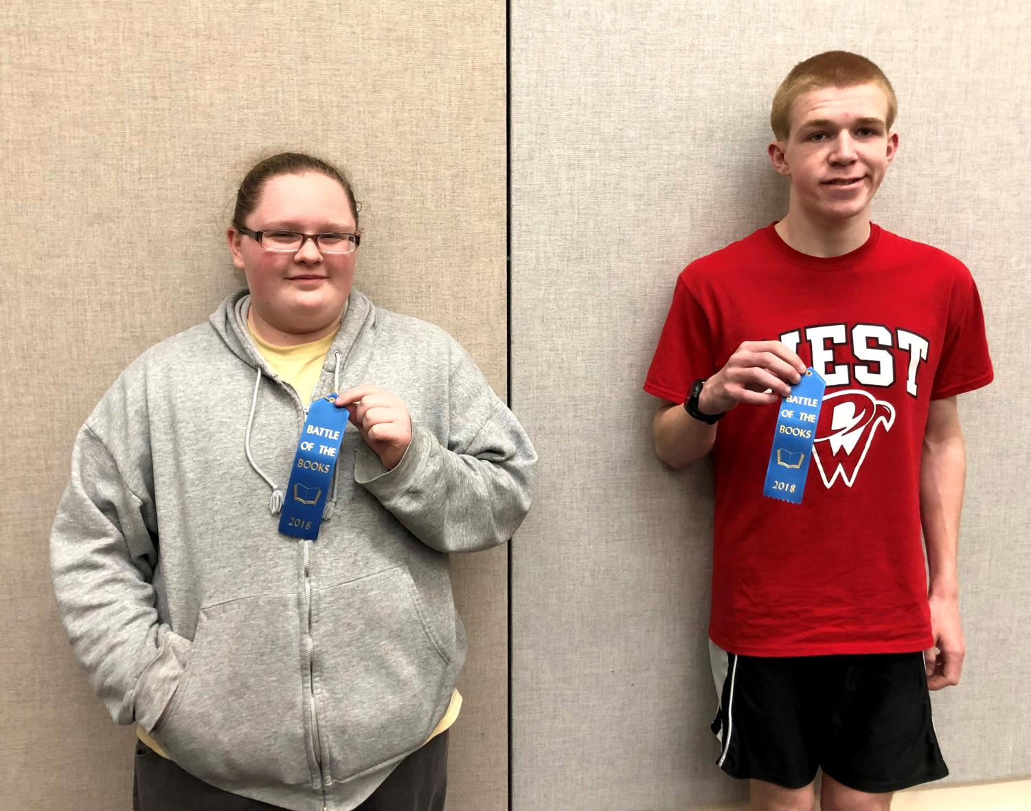 Senior Skylar Hintze (Left) and Junior Anton Kordick (Right) holding participation ribbons after the Battle of the Books competition (2017-18) at the Bettendorf Public Library.