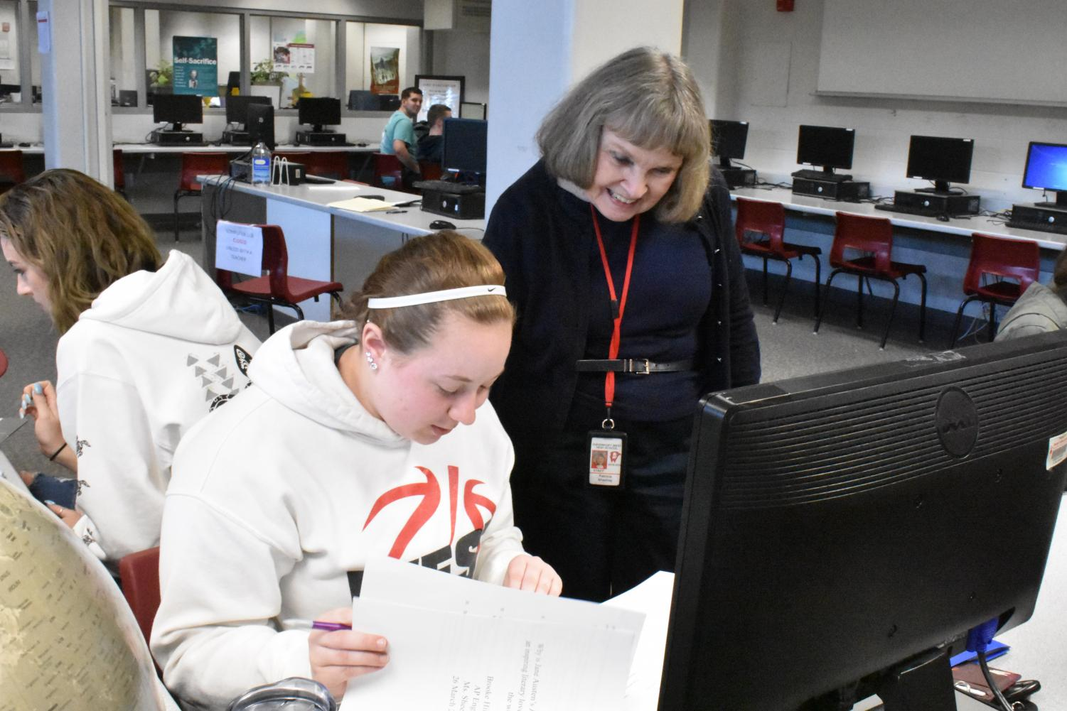 "Language arts teacher Pat Sheehey assists senior Brooke Hildebrant with paper revisions sporting a smile. ""I think it is very important to develop skills in English, and to write well, speak well, and to read,"" Sheehey said about the subject she has been teaching for the past 50 years."