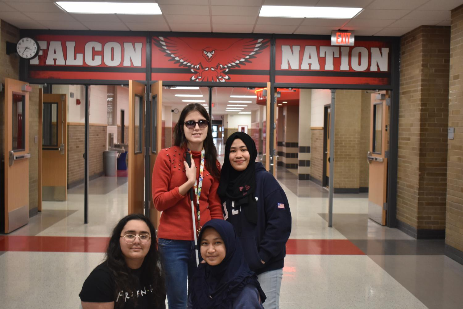 From left: Becca Saad (Lebanon), Andjela Ognjanovic (Serbia), Syafira Adani (Indonesia) and Farnaiza Gulam (Philippines) pose to show their Falcon spirit. These foreign exchange students are spending an academic year at Davenport West to experience what American high school life is like.
