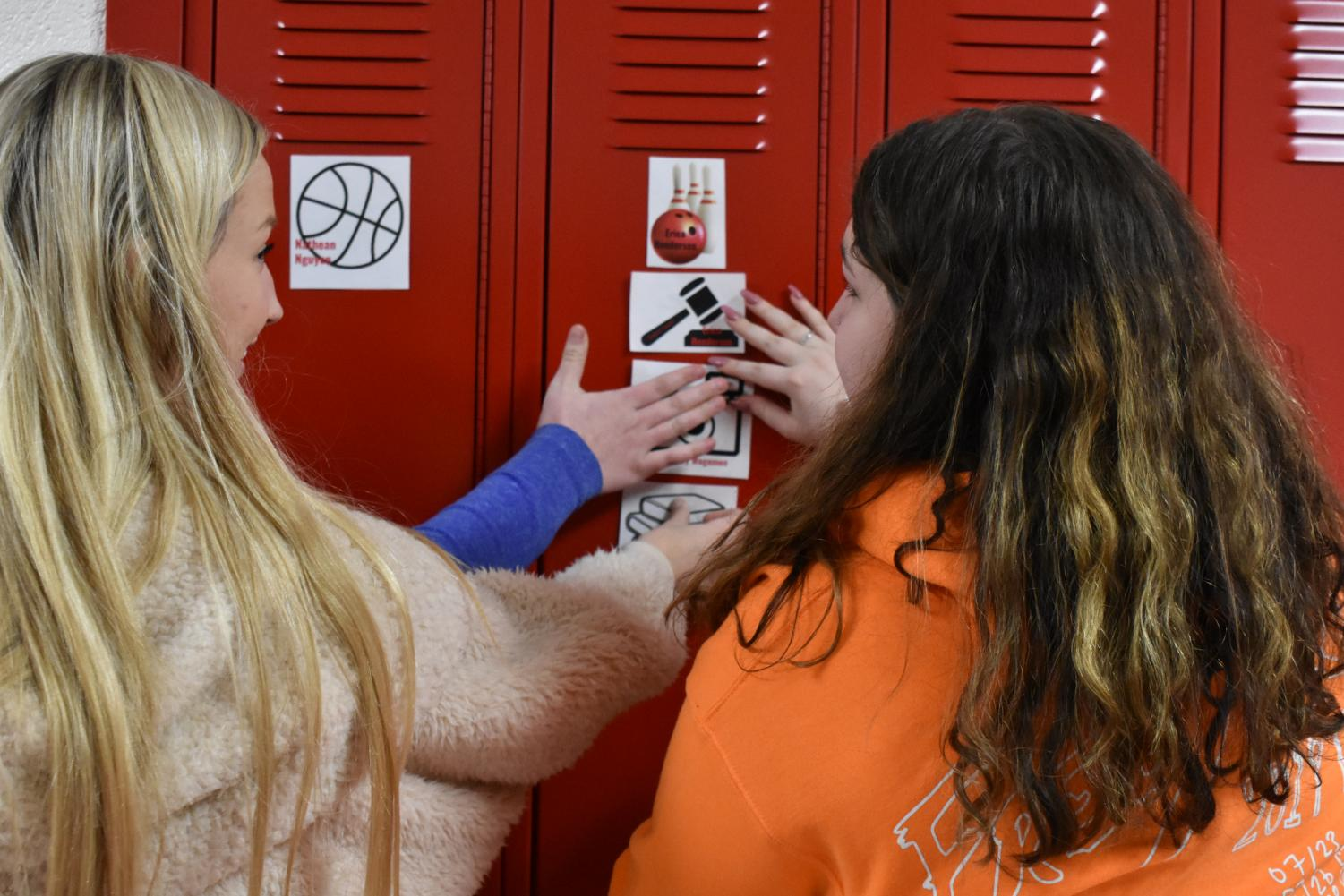 Student Senate members and seniors Erica Henderson, Hailey Hansen, and Gillian Collins put up locker tags to recognize students in the building and involvement in clubs and sports.