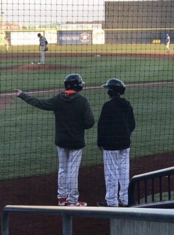 "McCrery (Left) and Parcel (Right) converse on the field during a River Bandits game. McCrery learned substantial amounts of insight while being a bat boy and was even taught some Spanish by some of the players. ""Jake loved his time as a bat boy and gained knowledge and experiences about baseball,"" R. McCrery said."