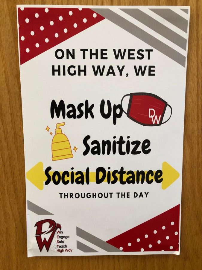 In+an+effort+to+lower+viral+spread%2C+posters+reminding+students+to+distance+and+sanitize+line+the+halls.+
