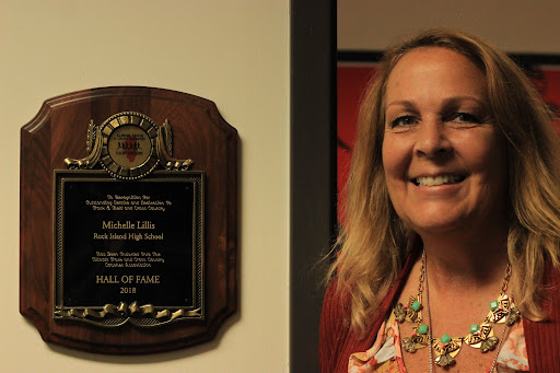 New athletic director Michelle Lillis stands proudly by her hall of fame plaque. She was recognized as the first female athletic director at her previous school, Rock Island High School.